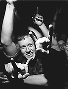 Young man in the middle of crowd smiling and making rock hand gesture.