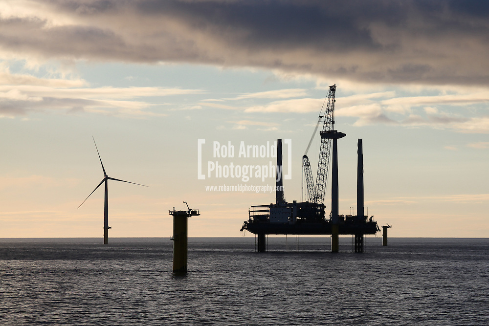 © Rob Arnold.  04/04/2014. North Wales, UK. Wind turbine installation vessel Sea Jack silhouetted in the evening sky over the Gwynt y Môr Offshore Wind Farm off the coast of North Wales. Photo credit : Rob Arnold