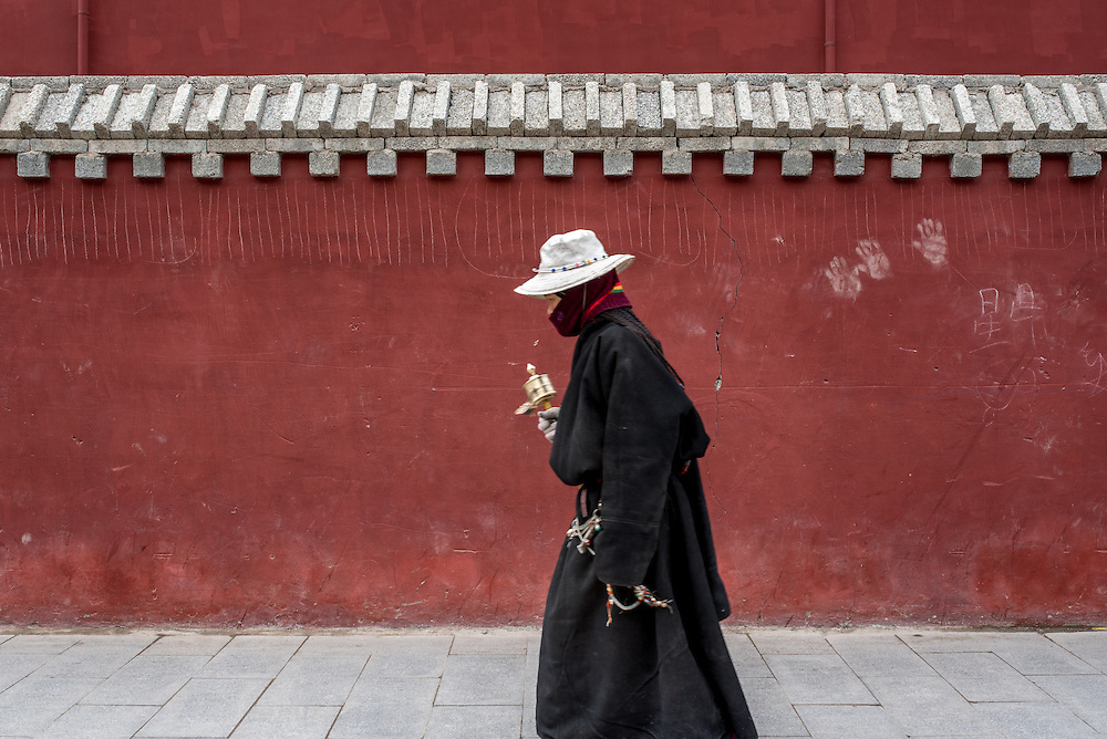 A woman walks around the Gyanak mani wall in Yushu prefecture, Tibet (Qinghai, China).