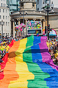 The giant Pride flag encourages high spirits - The London Pride parade and event in Trafalgar Square.