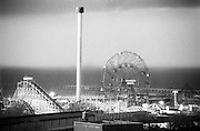 A view of Coney Island and the Wonder Wheel against and on coming storm .