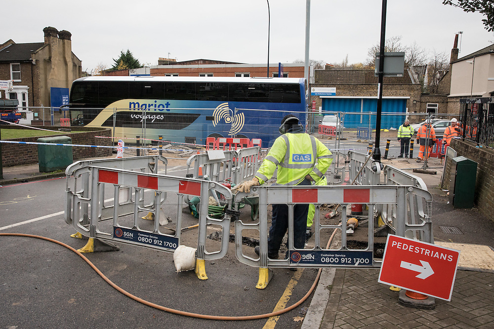 © Licensed to London News Pictures. 27/11/2016. London, UK. Gas contractors work to seal the gas mains after a tourist coach fell into a sinkhole in Lewisham. Lee High Road has been closed off and police declared a 'major incident' after the coach with 100 passengers on board fell into a sinkhole caused by a burst water mains, flooding a long stretch of the road including many local businesses. . Photo credit: Rob Pinney/LNP