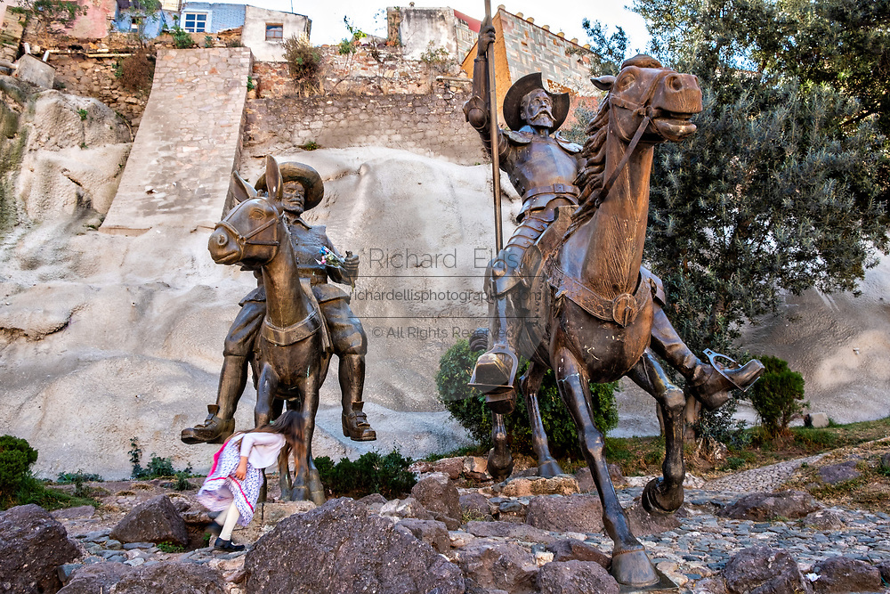 A little girl plays amongst the life-sized statues of Don Quixote de la Mancha and Sancho Panza at the bottom of a rock cliff in the historic center of Guanajuato City, Guanajuato, Mexico.