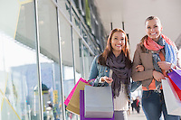 Happy female friends with shopping bags walking by store