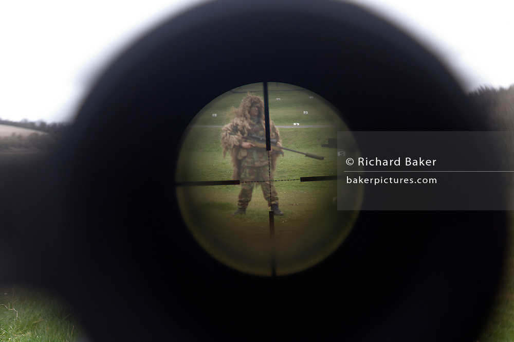 A camouflaged British infantry soldier is seen down the telescopic sight of the new British-made Long Range L115A3 sniper rifle on Salisbury Plain, Warminster, England. Sniping means concealment, observation and assassination, a strategy the British are using more against the Taliban in Afghanistan. Swiss Lapua .338 inch rounds (8.59mm) travel at sub-sonic speeds of 936 metres/sec, finding its target accurately up to 1,100 metres. The rifle weighs 6.8kg with telescopic image-intensified scopes to 25x life size vision, made by Schmidt & Bender. Front-mounted 'suppressor' minimises the signature normally compromising snipers' position. At £23,000 each, a £4 million contract has been awarded to Accuracy International, to provide the Army, Royal Marines and RAF. The British say this is the best sniper rifle in the world.
