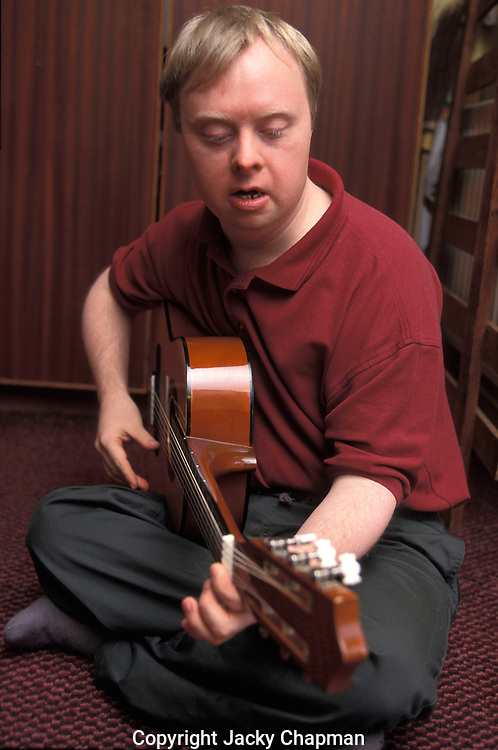 Young disabled boy playing guitar.