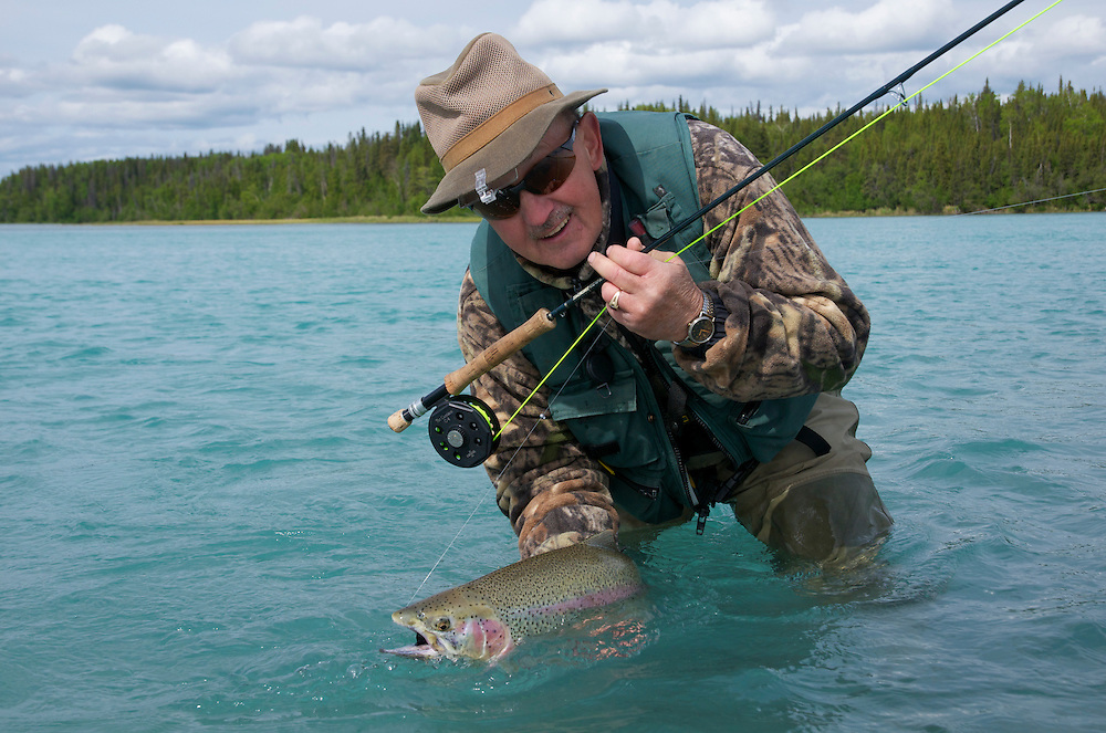 Trout fisherman holds a beautiful rainbow trout on the Kenai River.