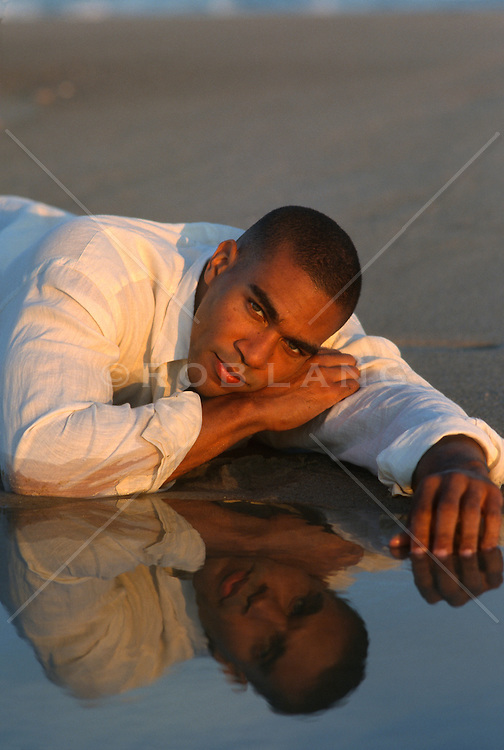 African American Man resting by a reflective body of water