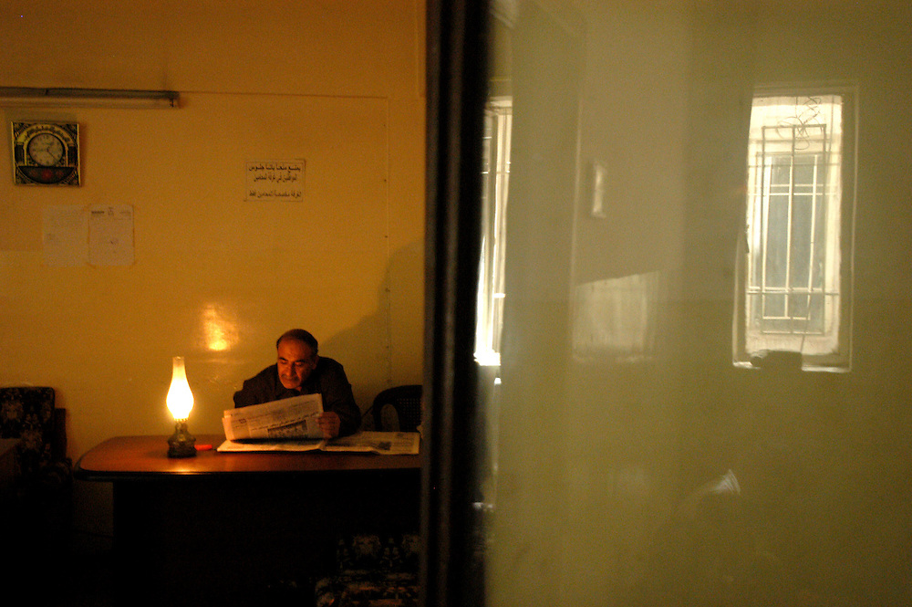 An official reads a newspaper by lamp light in a court justice building. One year after the war to topple the regime of Saddam Hussein, power cuts are still common place..Baghdad, Iraq. 24/04/2004.Photo © J.B. Russell