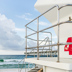 Lifeguard tower four and Gulf Pier in Pensacola Beach Florida. Pensacola Beach is on Santa Rosa Island in the Emerald Coast of the Southeastern United States of America. Photo is vertical and high resolution. Copyright ⓒ 2018 Paul Velgos with All Rights Reserved.
