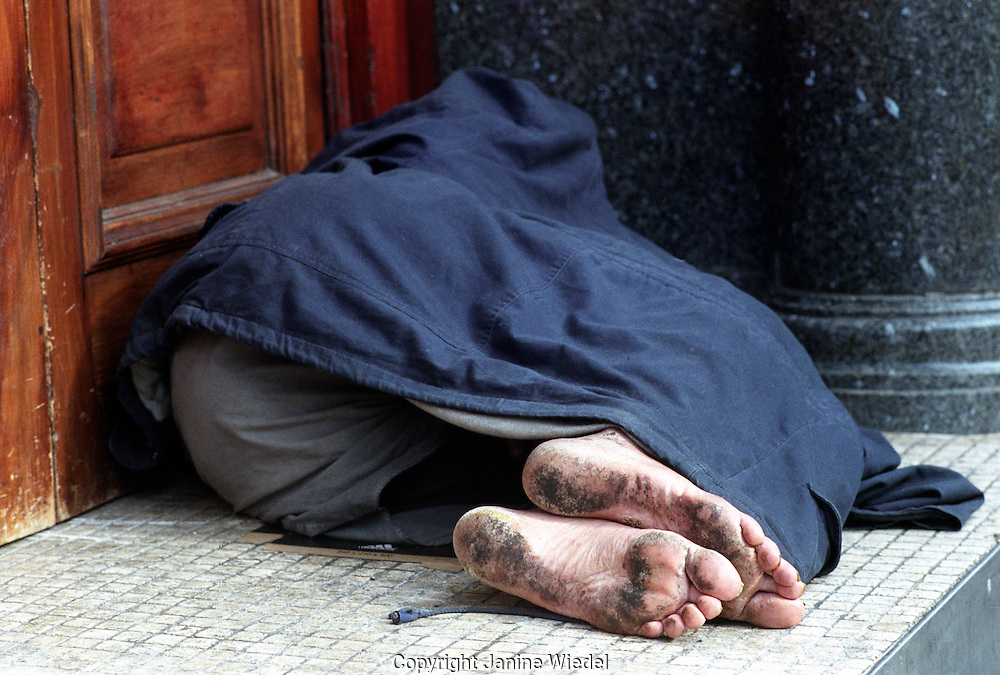 Homeless man asleep on the sidewalk in Leicester Square central London.