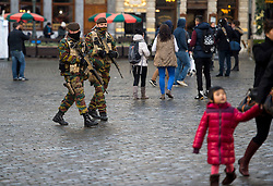 "© Licensed to London News Pictures. 23/11/2015. Brussels, Belgium. Belgian military patrolling past tourists in The Grand Place, the main square in central Brussels where the city is currently on lockdown amid ""imminent threat"" of Paris-style bomb and gun attacks. Some public transport and schools have been closed as a precaution. Photo credit: Ben Cawthra/LNP"