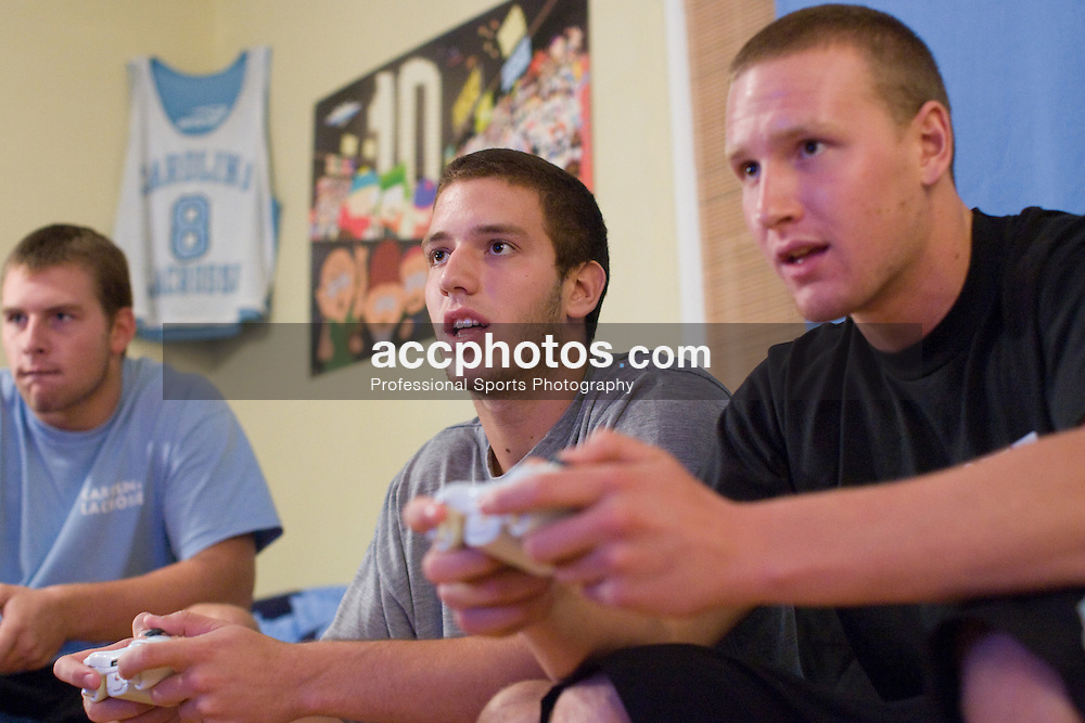 06 September 2007: North Carolina Tar Heels men's lacrosse members (L to R) Colin Sherwood, Chris Madalon and Sean Delaney play Xbox at their off-campus house in Chapel Hill, NC.