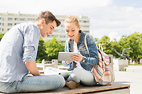 Young woman with male friend using digital tablet at college campus