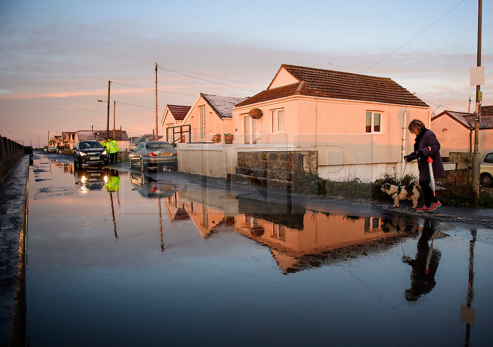 © Licensed to London News Pictures. 13/01/2017. Jaywick, UK. A woman walks her dog past surface water on the promenade, as police officers speak to local residents, along the seafront at Jaywick, Essex, where homes were expected to evacuated due to the threat of flooding in low-lying areas . Photo credit: Ben Cawthra/LNP