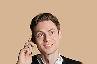 Happy mid adult man listening to mobile phone over colored background