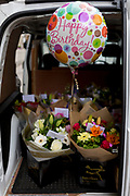 An inflated Happy Birthday helium balloon along with bouquets of fresh flowers in the rear of a van making multiple deliveries around the capital, on 5th June 2019, in London, England.