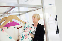 ROME, ITALY - 14 MAY 2014: Business owner Mina Giannandrea, 68, chooses a garment for a client in the Max Mara retail store she manages in Rome, Italy, on May 14th 2014. Ms. Giannandrea has owned 4 clothing store for 40 years, until last year, when she had to close two shops and fire 8 people due to high labour costs, tax hikes and big drop in domestic consumption. The shops are in two different Roman neighborhoods, and sell Max Mara garments.