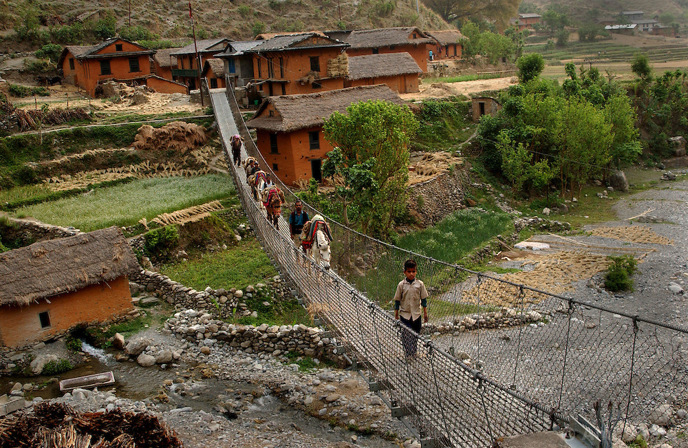 """RUKUM DISTRICT, NEPAL, APRIL 15, 2004:  Nepalese cross a bridge controlled by Maoists in Rukum district April 15, 2004. The infrastructure of Western Nepal is nonexistant and government troops have a hard time manoevering through the difficult terrain to combat the growing Maoist insurgency. Analysts and diplomats estimate there about 15,000-20,000 hard-core Maoist fighters, including many women, backed by 50,000 """"militia"""".  In their remote strongholds, they collect taxes and have set up civil administrations, and """"people's courts"""" to settle rows. They also raise money by taxing villagers and foreign trekkers. Though young, they are fearsome fighters and  specialise in night attacks and hit-and-run raids. They are tough in Nepal's rugged terrain, full of thick forests and deep ravines and the 150,000 government soldiers are not enough to combat this growing movement that models itself after the Shining Path of Peru. (Ami Vitale/Getty Images)"""