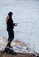 A woman fishes in the Neversink River in Cuddebackville, New York, on the opening day of trout season in New York State. Part of the riverbank in still covered in snow from the previous day.