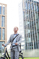 Happy businessman with bicycle standing outside office building