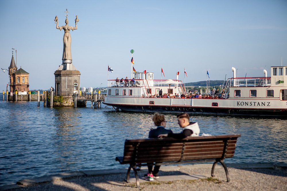 Visitors and inhabitants relaxing at the harbour of Lake Constance (Bodensee). In the back The Imperia which is a statue at the entrance of the harbour of Konstanz, Germany, commemorating the Council of Constance that took place there between 1414 and 1418. The concrete statue is 9 metres high, weighs 18 tonnes, and stands on a pedestal that rotates around its axis once every four minutes. It was created by Peter Lenk and clandestinely erected in 1993. The erection of the statue caused controversy, but it was on the private property of a rail company that did not object to its presence.