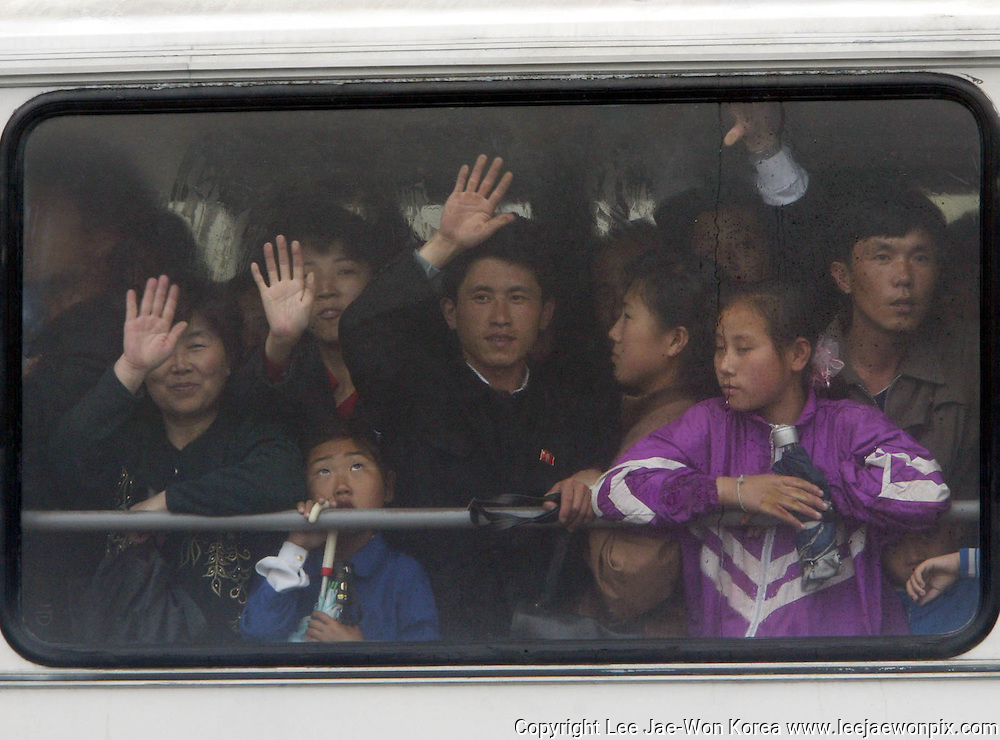 North Koreans on a bus wave in the capital Pyongyang. Photo by Lee Jae-Won (NORTH KOREA) www.leejaewonpix.com/