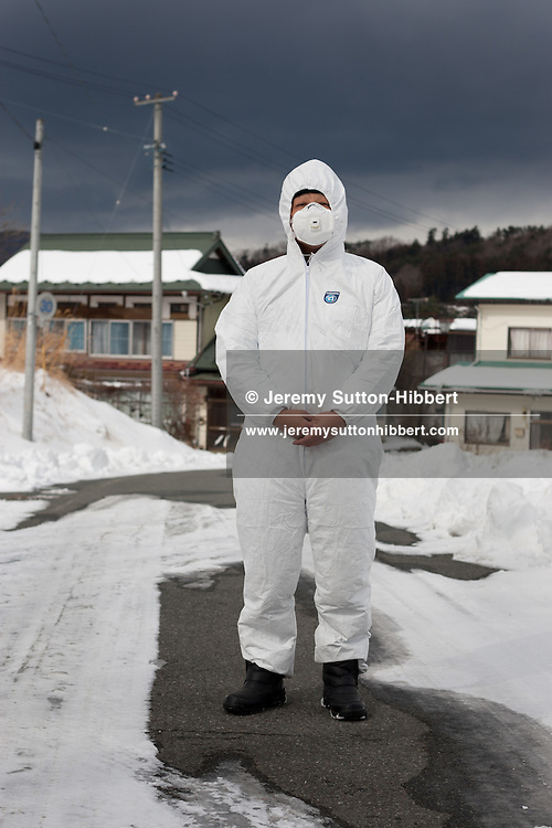 Ryuko Ishikawa (39 yrs old), a Buddhist priest whose temple Kannon-ji is situated in Namie town within the Fukushima nuclear exclusion zone, photographed wearing protective clothing in the highly radiated and now evacuated and deserted Iitate village, just outside of the nuclear exclusion zone, in Iitate, Tohoku, Japan, on Thursday 2nd February 2012. .Ishikawa-san had to flee his temple, in Namie, at the time of the Fukushima nuclear accident and does not envisage that he will be able to return to practice his Buddhism there again, due to the levels of radiation which not pollute the town.