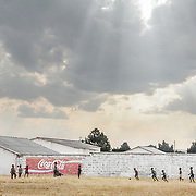 Africa villiage kids playing football on field next to school in Ndola, Zambia in front of Coca-Cola painted sign.