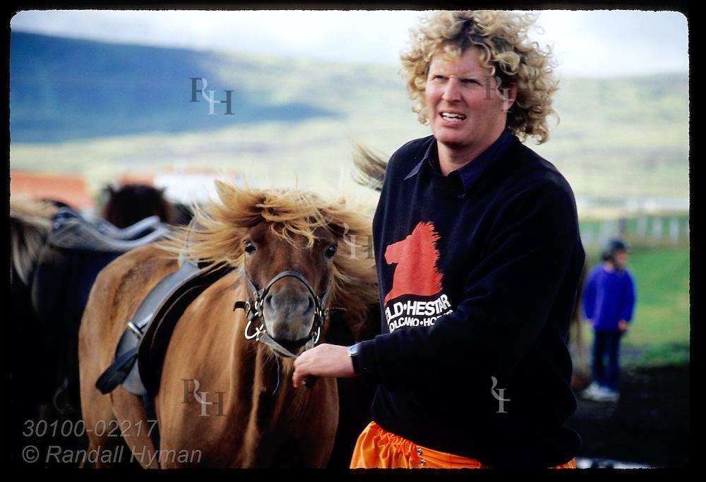 Hrodmar Bjarnason, founder and owner of Eldhestar horse trek company, pulls saddled-up horse to corral for trip; Hveragerdi, Iceland.