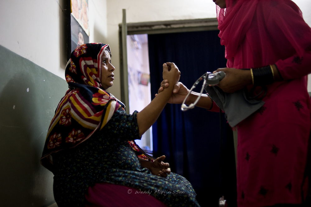 A young pregnant woman visits the local dai for a medical check up. <br /> Young birth attendants today are becoming more educated and work in a professional manner. They use the right equipment and work in better hygienic conditions. <br /> Most midwifes of the new generation have gone to school and followed a proper course instead of learning the trade from their mothers or grandmothers. Kandiaro, Pakistan, 2010