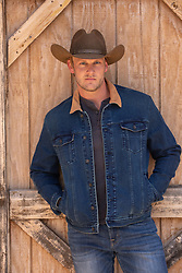 handsome blond cowboy by a rustic barn door