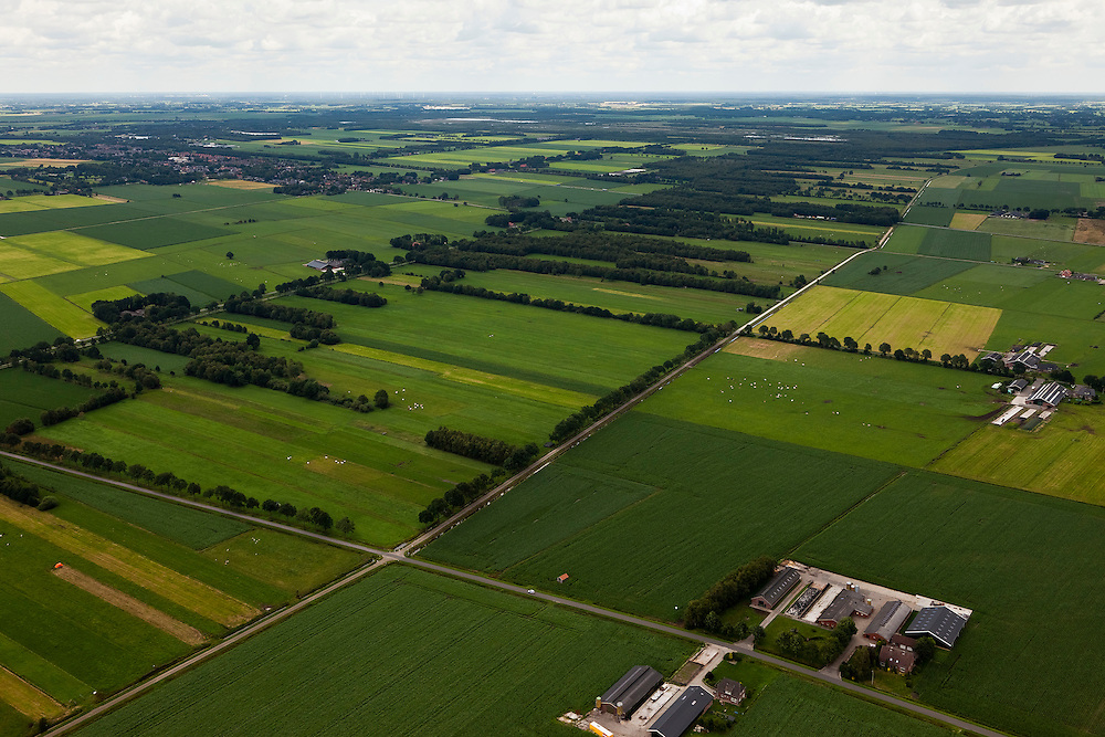 Nederland, Overijssel, Gemeente Twenterand, 30-06-2011; Landschap ten noorden Vriezenveen, met  aan de horizon Westerhaar-Vriezeenveensewijk. Voorbeeld van vroege ruilverkaveling (jaren '50). De oorspronkelijk (zeer) smalle en lange kavels, ontstaan door het ontginnen van veen, zijn samengevoegd tot grotere blokken en veelal is het kavelpatroon 90 graden gedraaid. De globale oorspronkelijke - onderliggende - structuur is deels nog herkenbaar..Kenmerkend zijn verder de 'boerderijstraten', linten van boerderijen omgeven door singels van bomen (diagonaal in het midden)..Landscape north of Vriezenveen, an early example of land consolidation (50s)..The original (very) long and narrow lots, created by the extraction of peat, are merged into larger blocks and in most cases the plot pattern has been rotated 90 degrees  The original - underlying - structure is still partly visible..Further characteristic features are the 'farm roads' with farmhouses surrounded by belts of trees..luchtfoto (toeslag), aerial photo (additional fee required).copyright foto/photo Siebe Sw