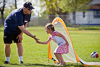 """Eric Allen, area manager for Skyhawks Summer Sports Camps, receives a """"low-five"""" from Talaiah Morgan, 6, during a soccer outing Thursday during the Borah Elementary's CDA4Kids program."""