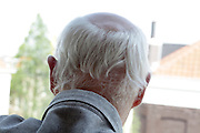 senior man with grey hair looking out of window