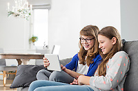 Happy sisters using digital tablet on sofa at home