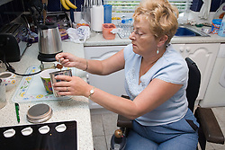 Woman wheelchair user making herself a cup of coffee,