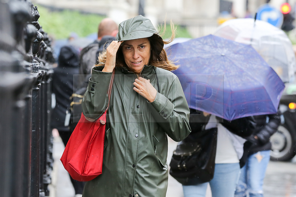 © Licensed to London News Pictures. 16/08/2019. London, UK. A woman shelters from the rain under a hood  in Trafalgar Square. The Met Office has issued a severe weather alert for most of today, as almost a month's worth of rain is expected in many parts of the UK. Photo credit: Dinendra Haria/LNP