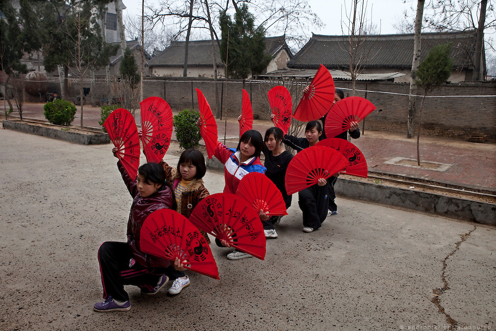 Students of the Taijuquan school practicing with the Tai Chi fan in the yard of the school