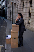 An office worker stands by a stack of office boxes on Fleet Street in the City of London.