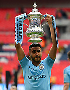 Riyad Mahrez (26) of Manchester City holds up the FA Cup at full time  during the The FA Cup Final match between Manchester City and Watford at Wembley Stadium, London, England on 18 May 2019.