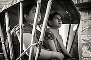Two women, passangers on a bicycle rickshaw in Varanasi (Benares), India.