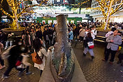 Tourist crowd around and pose for photographs with the statue of the dog Hachiko in Hachiko Square, Shibuya, Tokyo, Japan. Thursday December 5th 2019
