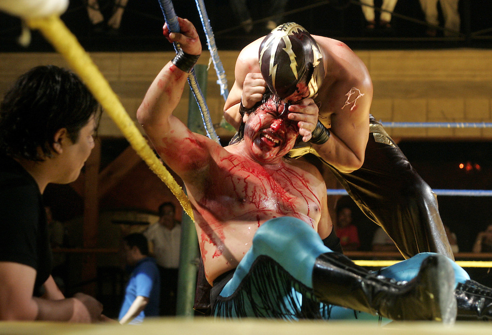 Halcon de Oro gets bitten by Poder 7 during a Lucha Libre match at McAllen's Club Fuego.