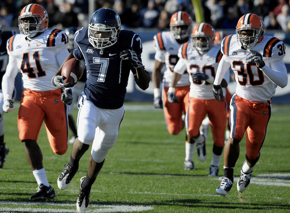 Connecticut's Mike Lang (7) is pursued by Syracuse as he scores a touchdown on a kick return in the first half of an NCAA college football game at Rentschler Field in East Hartford, Conn.