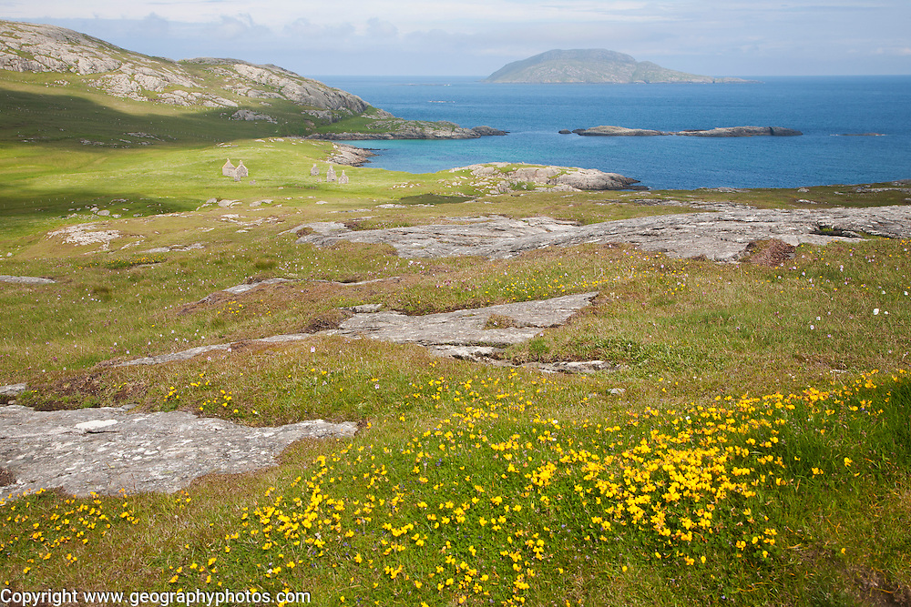 View over machair grassland to abandoned croft houses in the deserted village of Eorasdail, Vatersay Island, Barra, Outer Hebrides, Scotland, UK