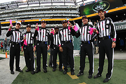 Oct 28, 2012; East Rutherford, NJ, USA; The officials for the game between the New York Jets and the Miami Dolphins show the pink flags presented to them by 11 year old Dante Cano at MetLIfe Stadium.