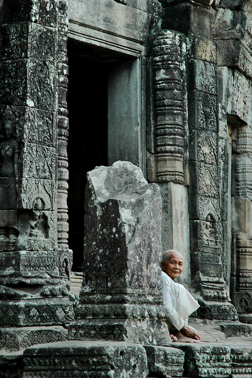 This Cambodian woman was relaxing in one of the many corridors of an interior building in the Angkor Thom temple complex which was built for King Suryavarman II in the early 12th century as his state temple and capital city. <br /> <br /> It is a massive three-tiered pyramid crowned by five lotus-like towers rising 65 meters from ground level is surrounded by a moat and an exterior wall. All the walls of the temple are covered inside and out with bas-reliefs and carvings including nearly 2000 apsara carvings representing some of the finest examples of apsara carvings in Angkorian era art.<br /> <br /> The ruins of Angkor, a UNESCO World Heritage Site with temples numbering over 1000, are hidden amongst forests and farmland to the north of the Tonle Sap Lake outside the modern city of Siem Reap, Cambodia. <br /> <br /> Quite a few of the temples at Angkor have been restored and represent a significant site of Khmer architecture.