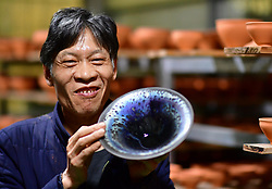 March 28, 2019 - Nanping, China - Wu Lizhu, inheritor of the workmanship of Jianzhan teaware, takes a piece of porcelain out from the kiln at his workshop in Jianyang District of Nanping City, south China's Fujian Province. Jianzhan teaware, a well-known Chinese porcelain originated in Jianyang, dates back to more than 1,000 years ago in Song dynasty (960-1279). Among all the Jianzhan teawares, the most rare and precious type is called ''Yaobian'', the workmanship of which has been lost for over 700 years. (Credit Image: © Xinhua via ZUMA Wire)