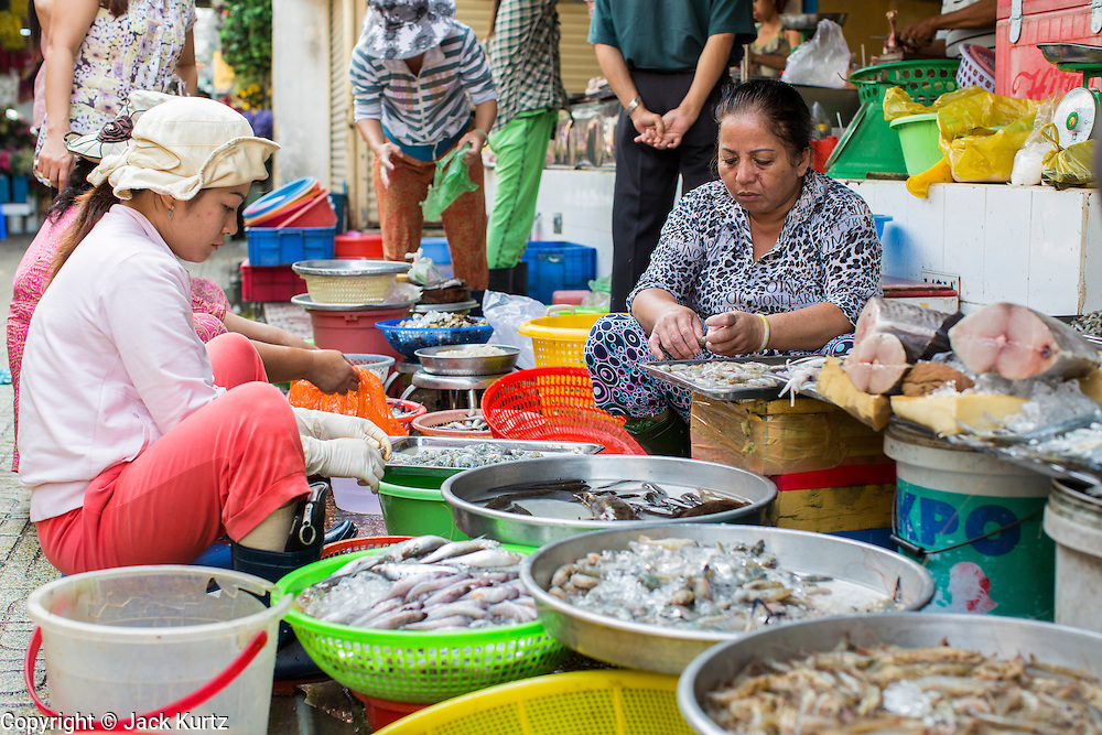 28 MARCH 2012 - HO CHI MINH CITY, VIETNAM:   Seafood vendors in the Ben Thanh Market in Ho Chi Minh City, Vietnam. Ben Thanh Market is a large market in the downtown area of Ho Chi Minh City (Saigon), Vietnam in District 1. The market is one of the earliest surviving structures in Saigon and one of the city's landmarks, popular with tourists seeking local handicrafts, textiles,ao dais (Vietnamese traditional dresses), and souvenirs, as well as local cuisine. The market developed from informal markets created by early 17th century street vendors gathering together near the Saigon River. The market was formally established by the French colonial powers in 1859. This market was destroyed by fire in 1870 and rebuilt to become Saigon's largest market. In 1912 the market was moved to a new building and called the New Ben Thanh Market to distinguish over its predecessor. The building was renovated in 1985.     PHOTO BY JACK KURTZ